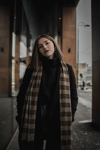 Portrait Of Young Woman In Warm Clothing Standing By Building