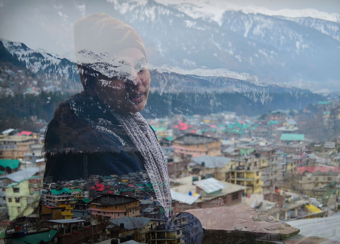 Double exposure of woman and townscape during winter