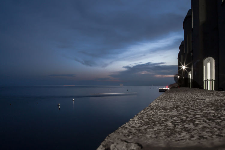 Retaining Wall By Sea Against Sky At Dusk
