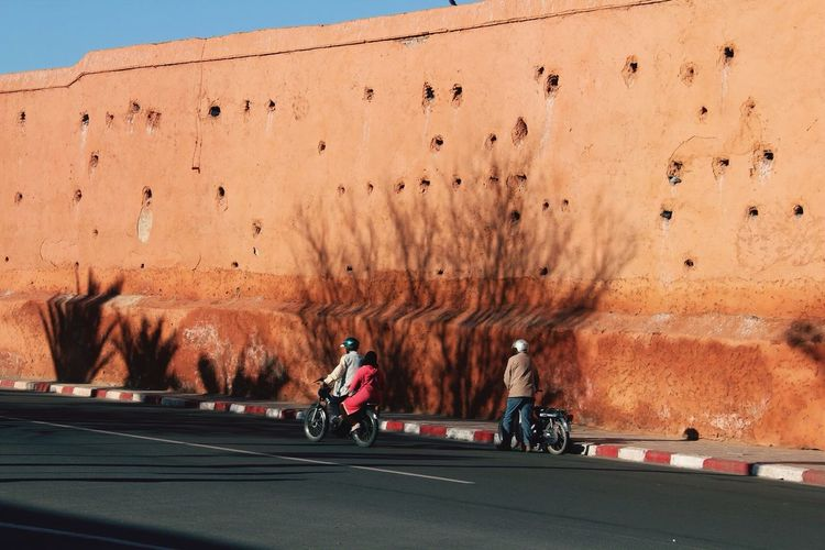 People On Motorcycles On Street Against Old Wall