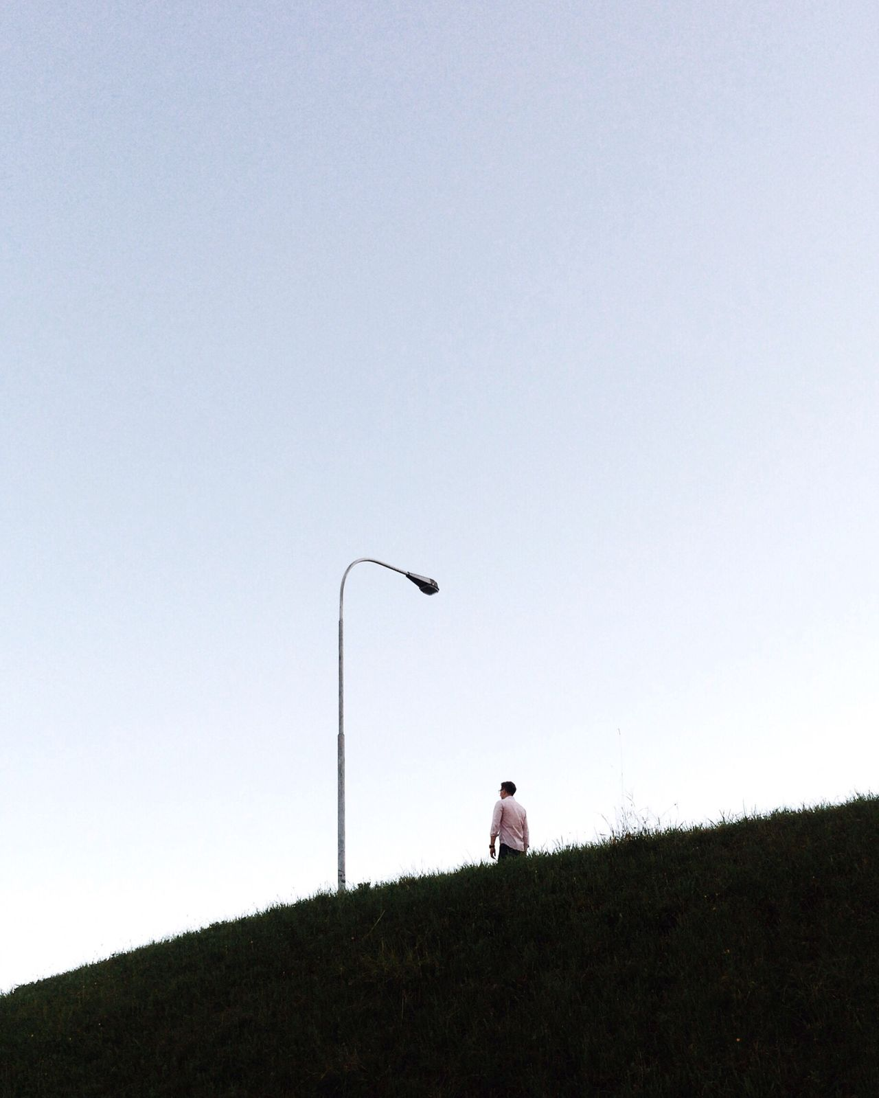 Low angle view of man walking on hill against clear sky during sunset
