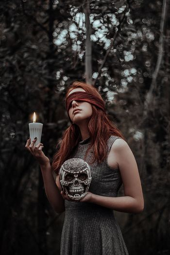 Woman holding candle against tree