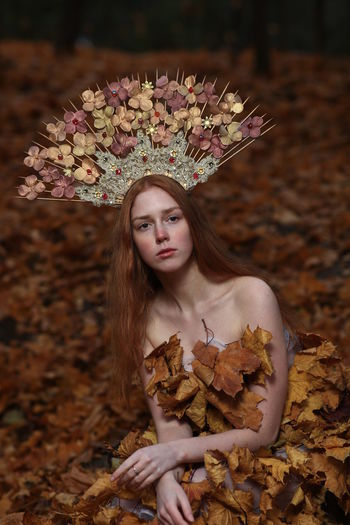 Portrait of young woman wearing flowers on hair sitting at forest during autumn
