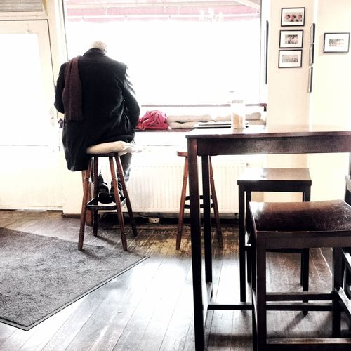 Rear view of man sitting on table at cafe