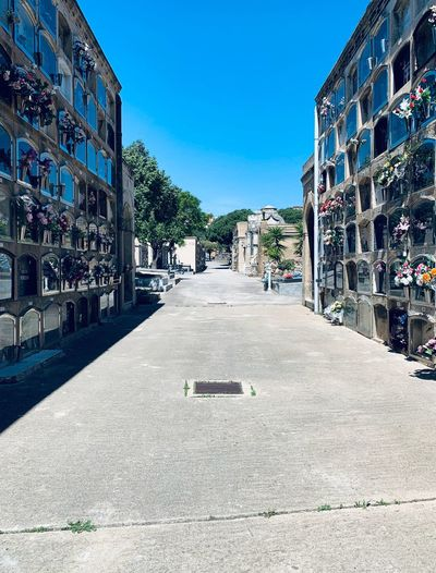 Empty road amidst buildings against blue sky
