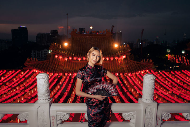 Portrait of young woman in city during chinese lantern festival at night