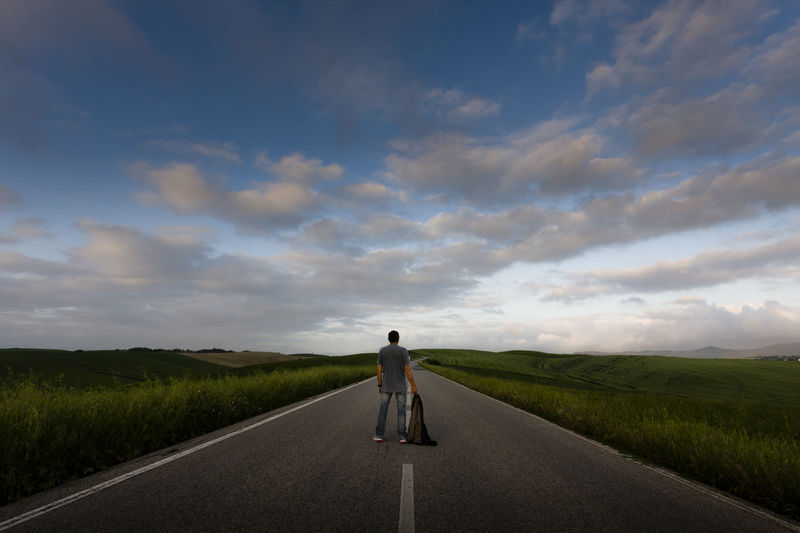 Rear view of man on road amidst field against sky