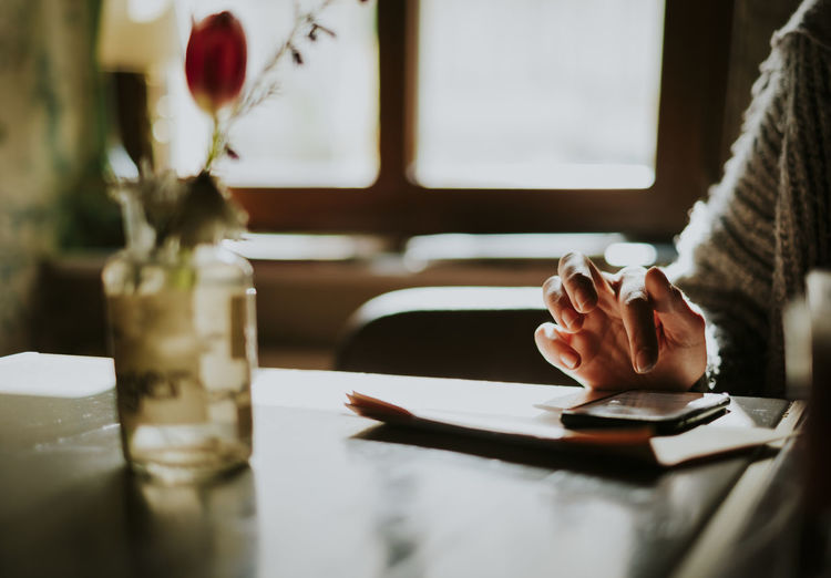 Cropped Hand Of Person Using Mobile Phone On Table At Home