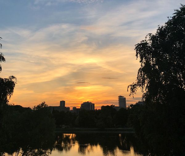 Silhouette buildings by lake against sky during sunset
