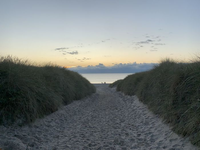 Footpath amidst sea against sky during sunset