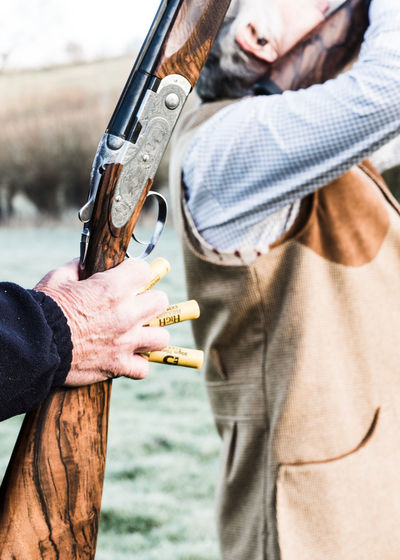 A loader holding a shotgun and cartridges between his fingers on a pheasant shoot. Holding Two People Day Focus On Foreground Midsection Nature Casual Clothing Men Real People People Outdoors Weapon Leisure Activity Sunlight Lifestyles Human Hand Shotgun Shotgun Shells Shotgun Cartridges Pheasant Season Pheasant Shoot Pheasant Shooting Country Life Hunting Shooting