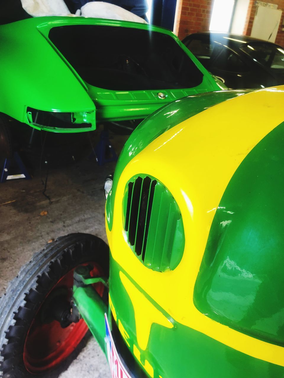 mode of transportation, green color, land vehicle, transportation, car, motor vehicle, yellow, day, no people, stationary, outdoors, multi colored, close-up, high angle view, travel, headlight, shopping, garage, wheel, junkyard