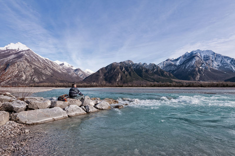 Man Sitting On Rock By Lake Against Mountains