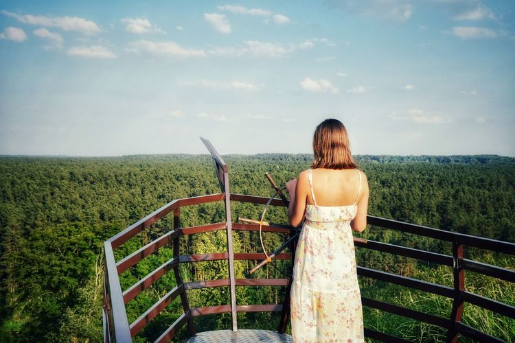 Rear view of woman standing at observation point against forest