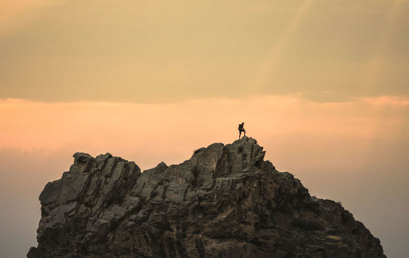 Man standing on rock by cliff against sky