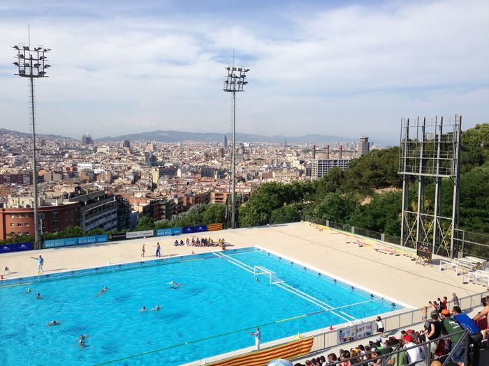 Audience looking at water polo with cityscape against sky