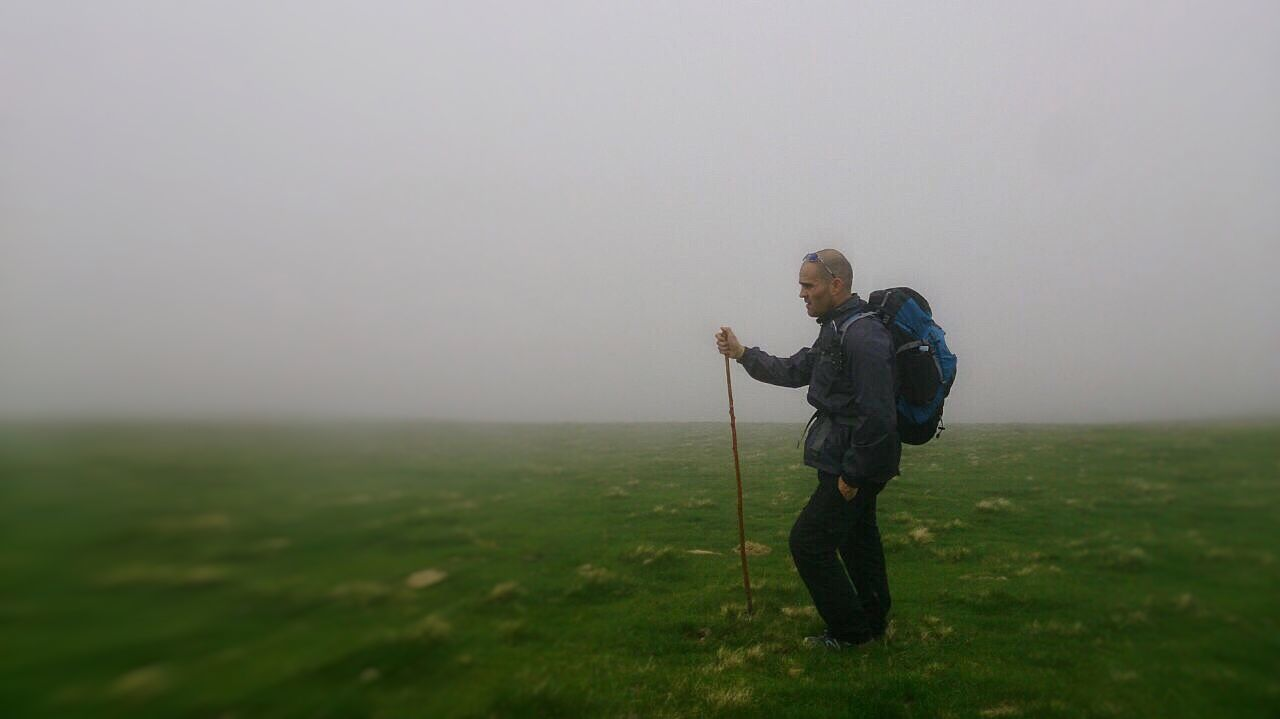 fog, grass, one person, full length, field, landscape, outdoors, holding, nature, standing, beauty in nature, day, sky, real people, men, scenics, one man only, adult, people, golfer, adults only