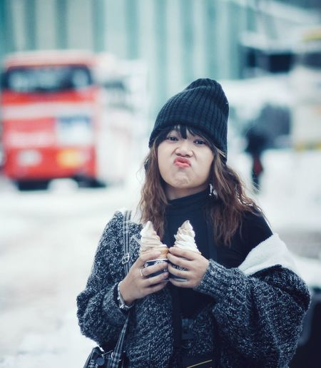 Winter Warm Clothing One Person Clothing Young Adult Cold Temperature Real People Adult Focus On Foreground Waist Up Scarf Lifestyles Holding Young Women Snow Front View Hair Standing Outdoors Wireless Technology