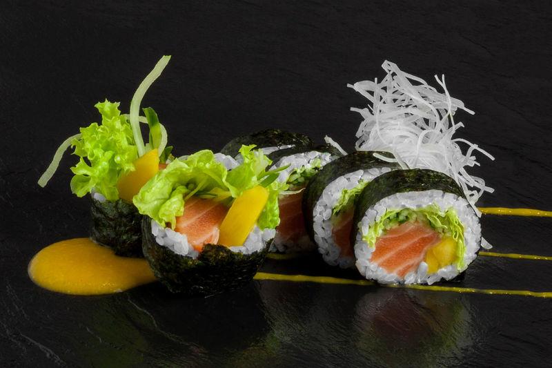 Close-up of sushi over black background