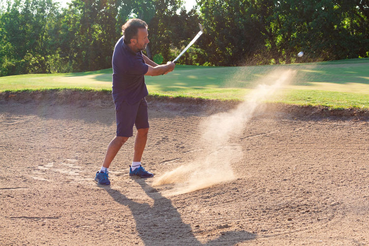 Man golfer take a shot in the bunker - play golf in the bunker