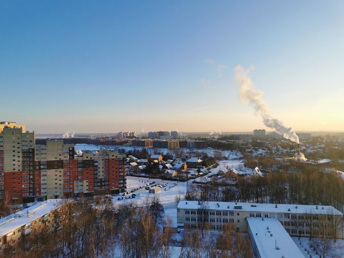 Smoke emitting from factory against clear sky during winter