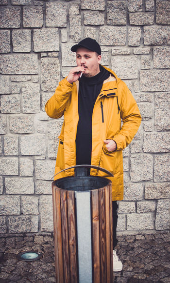 Man smoking cigarette while standing by garbage bin against wall