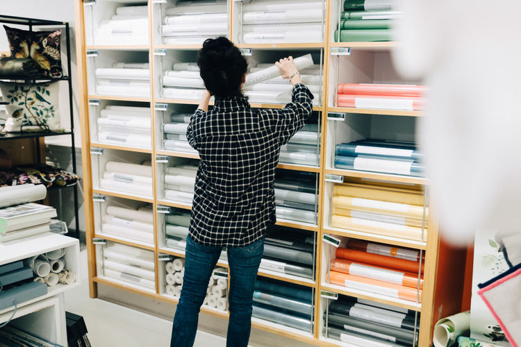 Rear view of woman reading book in store