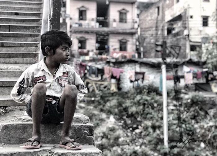 Boy sitting against buildings in city