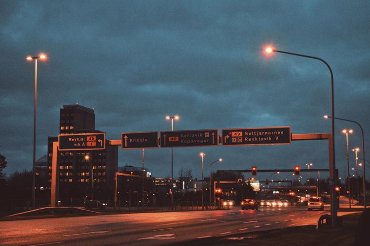 Illuminated road sign at night