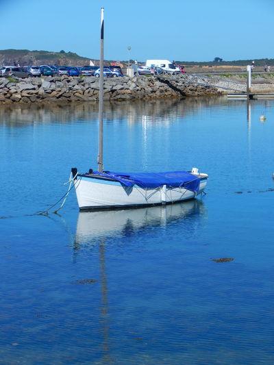 Sailboat moored in sea against sky