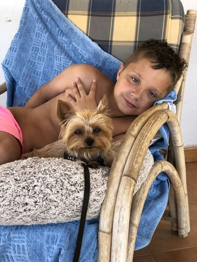 Portrait of cute boy with dog at home