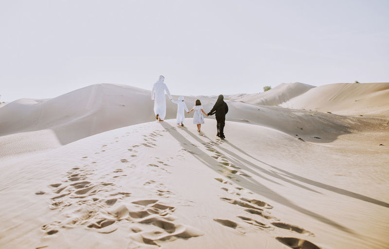 Rear view of family walking on sand dune
