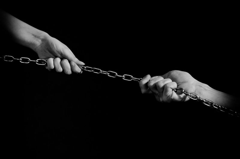 Cropped Hand Of People Pulling Chain Against Black Background
