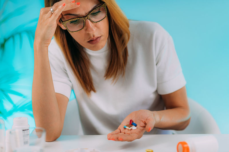 Female patient failing to follow medical advice, demonstrating prescribed medicine