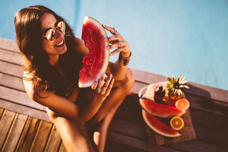 Cheerful Eating Enjoyment Food Food And Drink Freshness Fruit Happiness Healthy Eating Holding Lifestyles One Person Outdoors Plate Real People Sitting Smiling Summer Sunglasses Sunlight Watermelon Women Young Adult Young Women