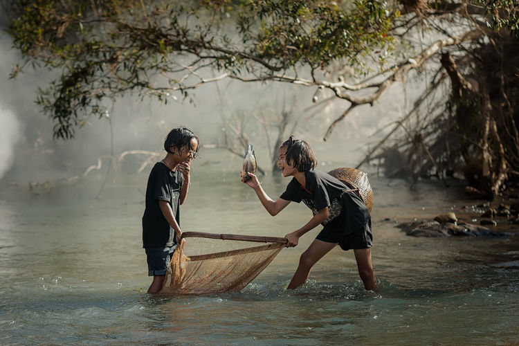 Rural children fishing at the river. Adult Casual Clothing Child Day Lake Leisure Activity Lifestyles Men Nature Outdoors People Plant Real People Standing Togetherness Tree Two People Water Waterfront Women