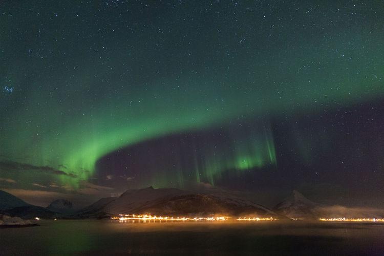 Idyllic shot of aurora borealis over lake against sky at night