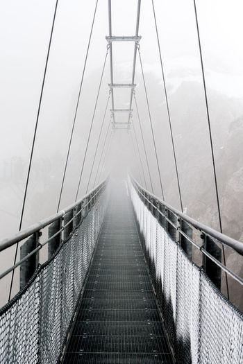Empty narrow footbridge against the sky