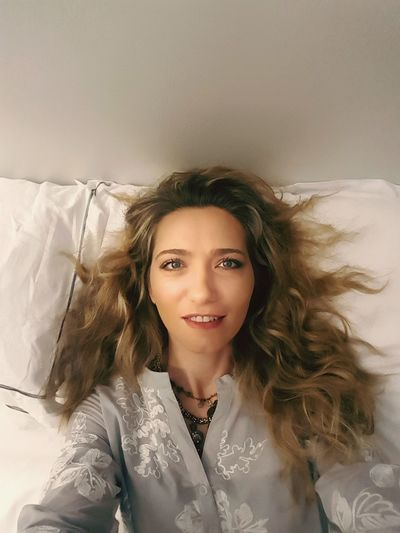 Portrait of smiling young woman relaxing on bed at home