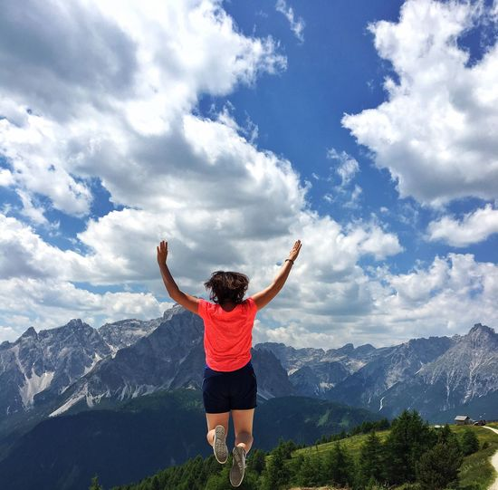 Rear View Of Woman Jumping Against Cloudy Sky