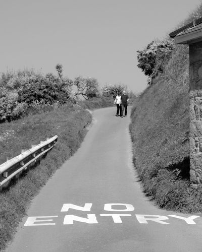 Two people who obviously entered! An empty road with a huge 'No Entry' sign emblazoned upon it and a couple walking arm in arm in the distance. Clear Sky Day Greve De Lecq Jersey Channel Island UK Monochrome No Entry No Entry Sign Outdoors People On A Road Real People Road Sunny Afternoon