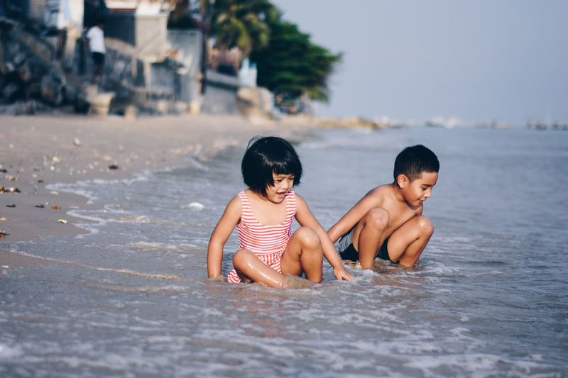 Cute siblings playing in sea on shore at beach