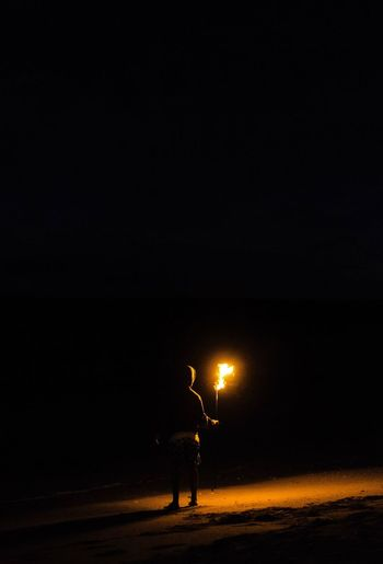 Silhouette man standing on illuminated street against sky at night