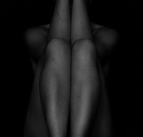Naked woman sitting against black background