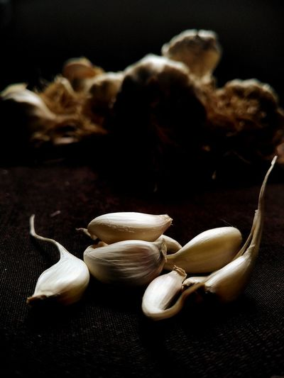 Close-up of garlic on table against black background