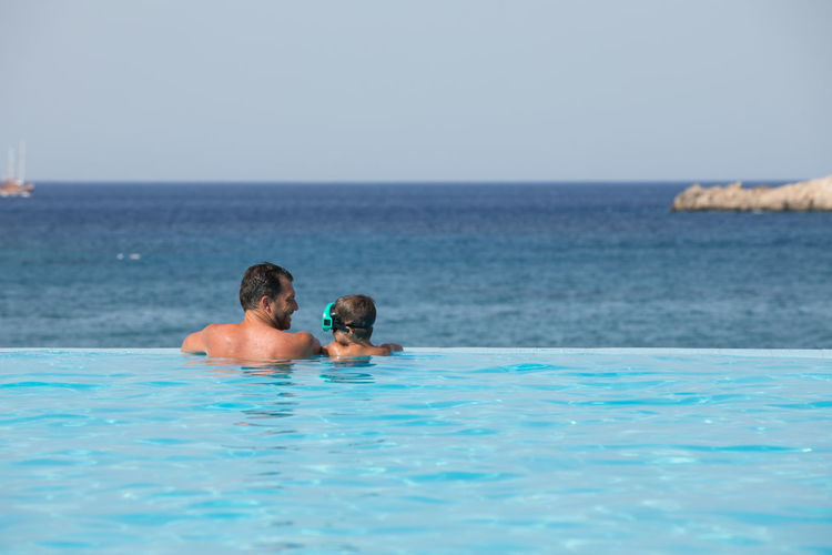 Rear view of father and son in infinity pool