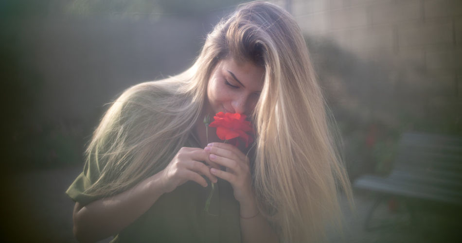 Woman with eyes closed smelling red flower