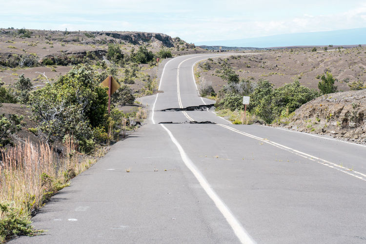 Broken from earthquake road passing through landscape against sky