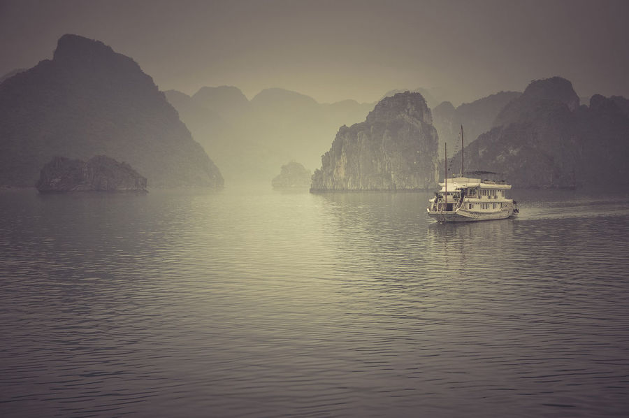 Misty Halong bay (Ha Long), Vietnam, in a rainy day. Filtered and toned image Cruise Ship Ha Long South China Sea Tonkin Gulf Vietnam Beauty In Nature Boat Filtered Image Ha Long Bay Ha Long Bay Cruise Island Limestone Nature Outdoors Scenics - Nature Sea Seven Natural Wonders Of The World Ship Sky Toned Image Tranquil Scene Tropical Vintage Water Waterfront