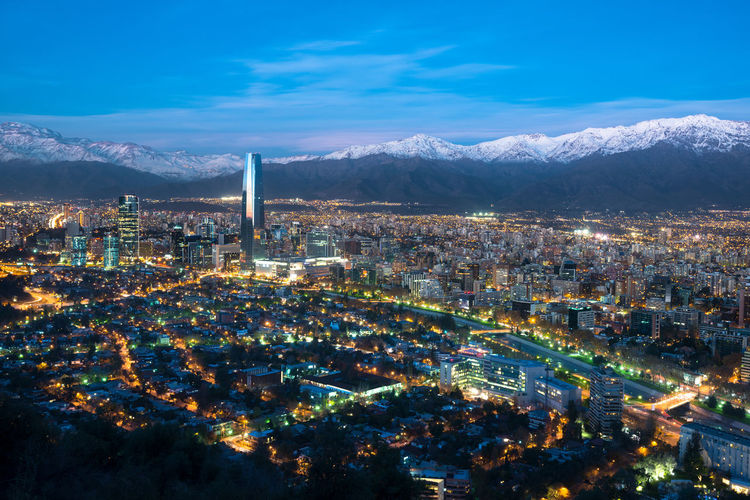 Aerial View Of Illuminated Cityscape Against Snowcapped Mountains During Sunset